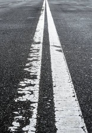 Asphalted road with two continuous faded white strips. White road divider lines of a highway. Long banner format. Two-way asphalt road, close up of the dividing road strip. Stock fotó