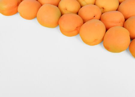 Apricot on a white background, arranged on top right corner, with copy space. Top view, close up.