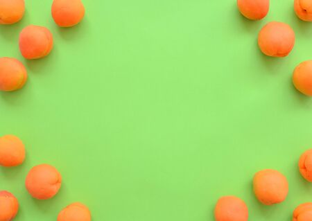 Apricots on a green background, arranged in corner frame, with copy space. Top view, close up. fruit frame