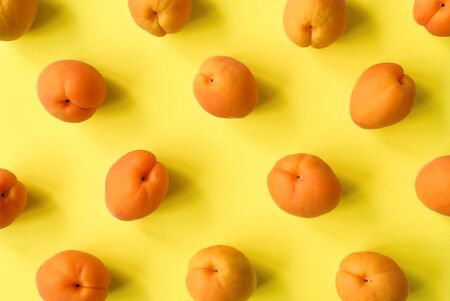 Apricot on bright yellow background. Apricot pattern. Top view, flat lay. Summer fruit