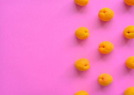 Apricot on bright pink background. Apricot pattern. Top view, flat lay. Summer fruit. Copy space