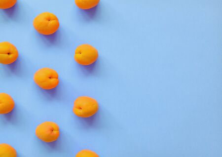 Apricot on light blue background. Apricot pattern. Top view, flat lay. Summer fruit. Copy space