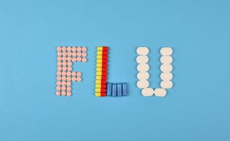 Flu season or influenza concept. The word flu made from the assorted pills and capsules on blue background. Pharmacy theme, health care, drug prescription for medication treatment