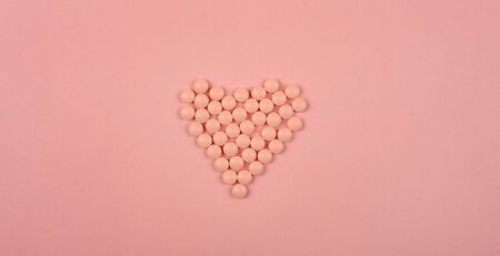 World Heart Day concept. Medical background. Pink Pills in form of heart on pink background. Flat lay. Heart health concept.