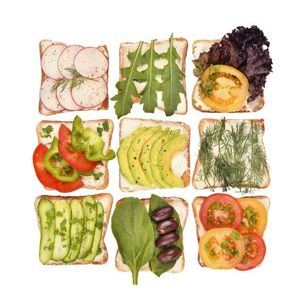 Toasted bread and different toppings isolated on white background, top view. Toasts with avocado, spinach, arugula, tomatoes and other vegetables ingridients. Healthy snack or vegan food concept