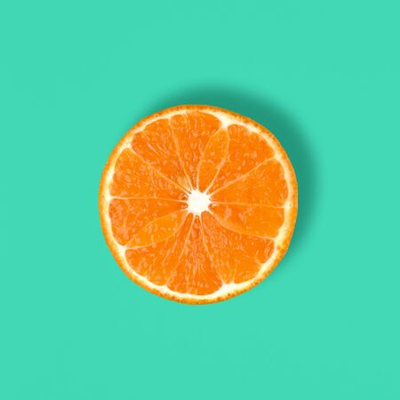 Cut Mandarin fruit isolated on a blue or mint background. Ctrus round slice. Food background. Top view, flat lay..
