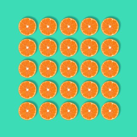 Fruit pattern of fresh mandarin slices isolated on blue or mint background. Flat lay, top view. Pop art design, creative summer concept. Half of tangerine citrus in minimal style.
