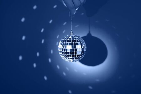 Mirror or disco ball, reflecting colorful lights on classic blue background. Party banner with copy space.