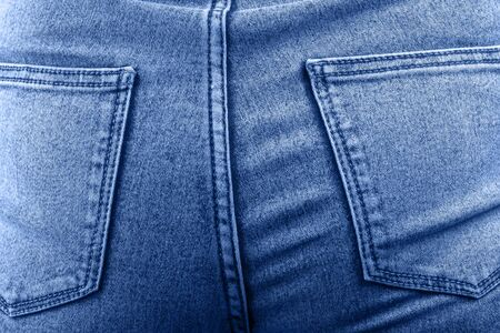 Female hips in jeans close up. Woman wearing jean pants from back. Female bottom in light blue tight jeans
