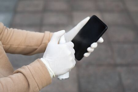 Young woman disinfects her phone with a hand sanitizer. Woman holding a mobile phone in her hands wearing latex protective gloves at the street in public place. Banque d'images