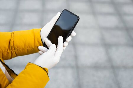 Young woman holding a mobile phone in her hands wearing latex protective gloves at the street in public place. Coronavirus spreading precautions measures concept.