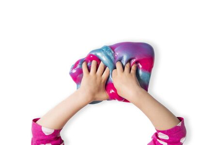Child hands and colorful pink, blue and purple shiny slime. Child girl plays with slime isolated on white. Home educational games concept. Top view, flat lay banner.