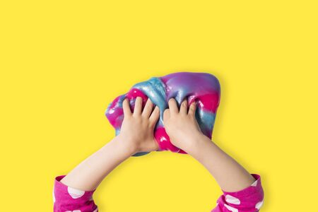 Child hands and colorful pink, blue and purple shiny slime. Child girl plays with slime isolated on bright yellow background. Home educational games concept. Top view, flat lay banner. 免版税图像
