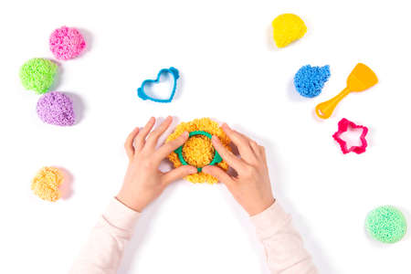Girl playing playfoam at home isolated on white background. Top view. Home Education game with clay. Early development DIY concept. Hands play with modeling clay and make circle
