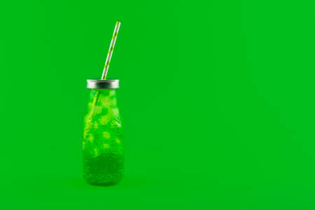 Lemonade or Cocktail Drink in coctail glass with straw and ice isolated on green background. Summer drink poster or banner with copy space.