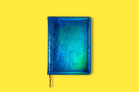 Neon Green and blue closed notebook mockup isolated on yellow background. Top view on mock up of notepad Standard-Bild