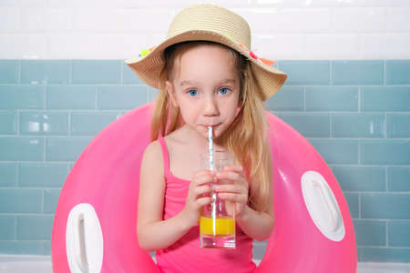 Funny sad little girl with a pink rubber ring, wearing a hat and having a cocktail in the bathroom. Quarantine vacation concept.