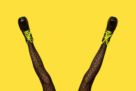 New gray female boots with bright yellow laces on long slender woman legs in gray tiger print tights isolated on yellow background. Pop art concept banner with copy space.