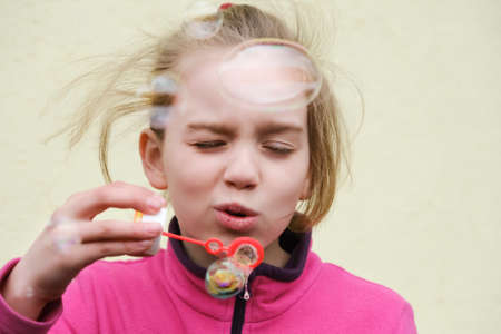 Girl smiling and blowing soap bubbles. Funny outdoors activity.