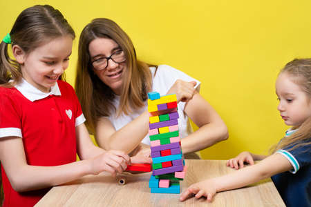 A happy family playing a round tower game with wooden blocks with their lovely daughters. Mother and daughters have fun playing the tower game.
