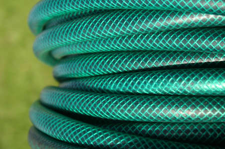 plastic conduit: Coiled green garden hose