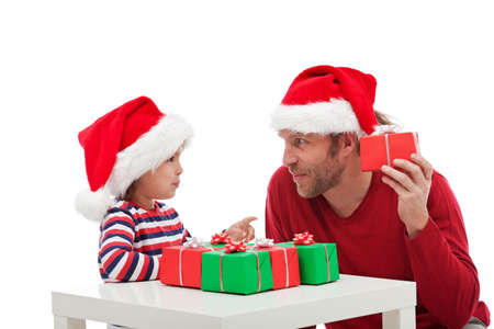 Father and son holding gift boxes with santa hat in had - isolated photo