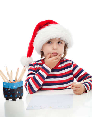 Little boy thinking about writing a letter to Santa photo