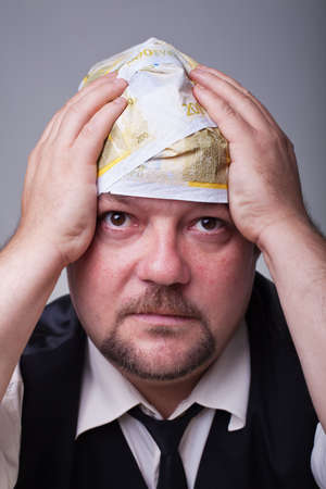 prompting: Businessman with financial problems prompting his head with his hand Stock Photo
