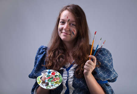 smeary: Young painter with smeary face holding palette and paintbrushes