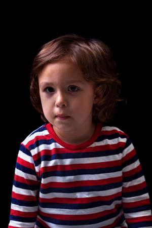 woeful: Cute little boy portrait isolated on black