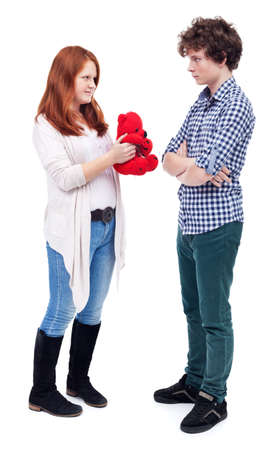sullen: Young girl offering teddy bear with red heart her boyfriend - isolated