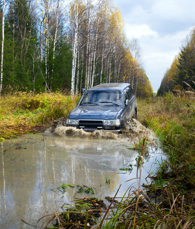 NIZHNY TAGIL. RUSSIA - JUNE 12, 2013: The third stage of the Russian Cup for Cross-Country Trials. Wheel drive vehicle leaves the swamp