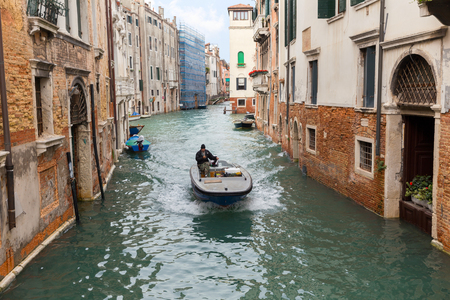 VENICE, ITALY - NOVEMBER 04, 2013: Motor boat carries the load on the canal in Venice. Venice is one of the worlds most popular tourist destinations with 21 million visitors per annum Editorial