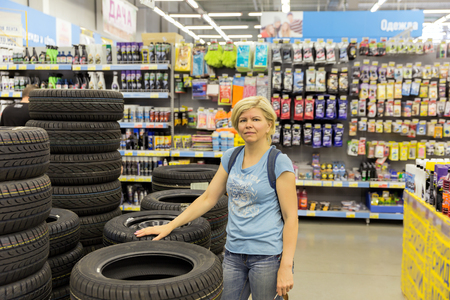 warehouse: Woman chooses the wheel for a car in a supermarket Stock Photo