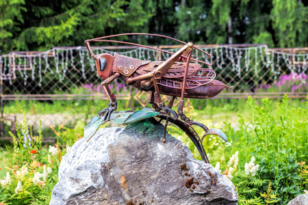 Nizhny Tagil, Russia - June 07, 2016: Monument to the grasshopper. Grasshopper from rusty metal sits on a rock
