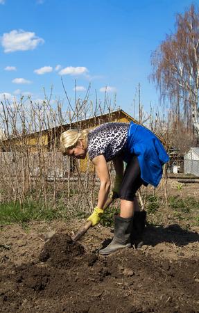 Vrouw werkt met schop in lentetuin