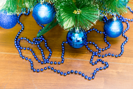 Blue balls on the Christmas tree and garlands on the wooden table
