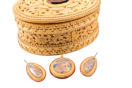 Casket from birch bark, medallion and earrings on a white background
