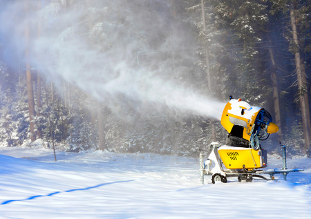 Snow gun on the background of the winter forest
