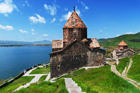 Panoramic view of Sevan Peninsula with both Churches of Sevanavank Monastery - Holy Apostles and Holy Mother of God, on the green meadow and with the pure Sevan Lake on the background, Armenia
