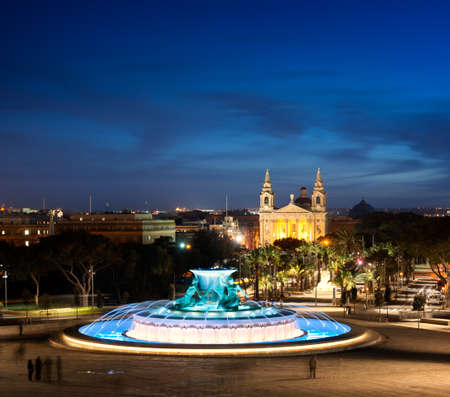 Night view at the Triton Fountain near the city gates of Valletta, Malta