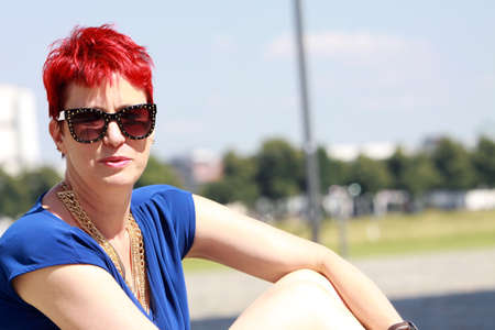 sympathetic: red-haired woman of about 50 in blue dress, Cologne, North Rhine-Westphalia, Germany