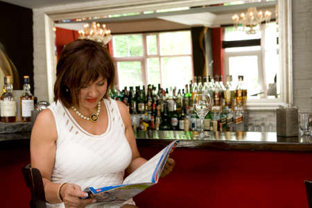 sympathetic: Woman in white dress sitting on a bar counter