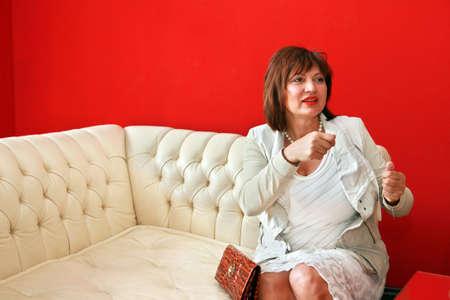 leren bank: elegant woman on white leather sofa