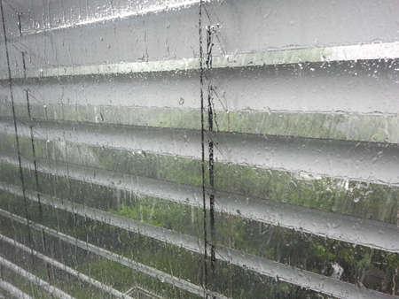 Blinds op verregende window Stockfoto