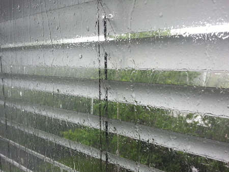 Blinds op doorweekt venster Stockfoto