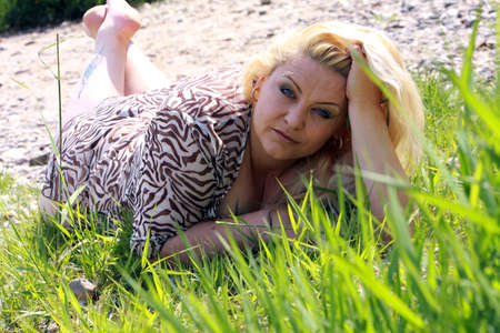 corpulent: Woman of about 40 with long blond hair lying in the grass