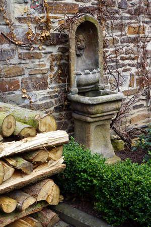 garden fountain: Burning wood and fountain in the garden Stock Photo