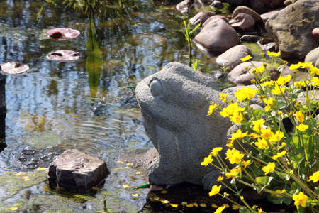 stonemason: water spewing frog at garden pond