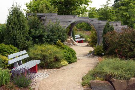 Parklandschaft mit Sitzbank und Durchgang